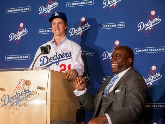 Los Angeles Dodgers new right-handed pitcher Zack Greinke, left, talks to the media as team owner Magic Johnson laughs, right, after during a baseball news conference at Dodgers Stadium Club,  Tuesday, Dec.11, 2012, in Los Angeles. Greinke moves up the freeway to join the Dodgers' starting rotation in a $147 million, six-year deal after spending part of last season with the rival Angels. (AP Photo/Damian Dovarganes)
